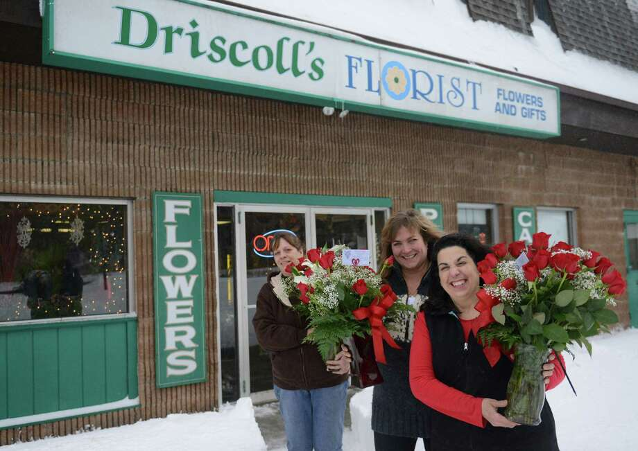 A group of employees, from left, Sandy Simonelli, Nancy Jagemann, and Trish Travis, hold flower arrangements outside of Driscoll's Florist in Danbury on Thursday. The florist was unable to deliver the arrangements because of the snowstorm that hit the day before Valentine's Day and hurt business at local flower shops. Photo: Tyler Sizemore / The News-Times