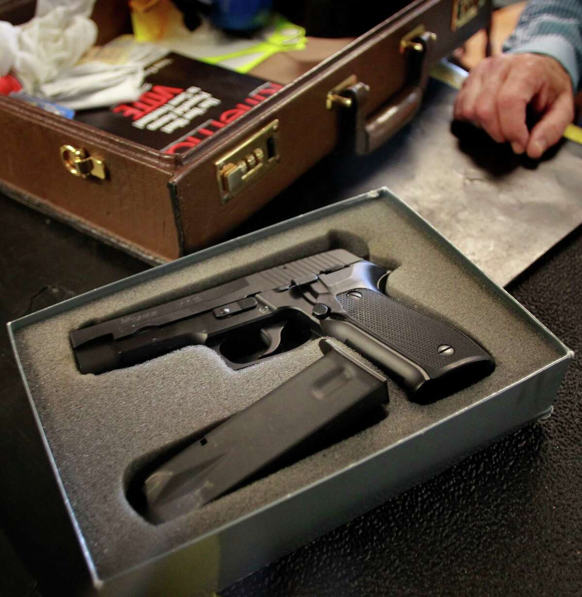 Gun owner Jeff Levinger shows how his weapon must be legally transported: unloaded and locked in a case, and carried separate from the ammunition, as he arrives at the Jackson Arms shooting range in South San Francisco.