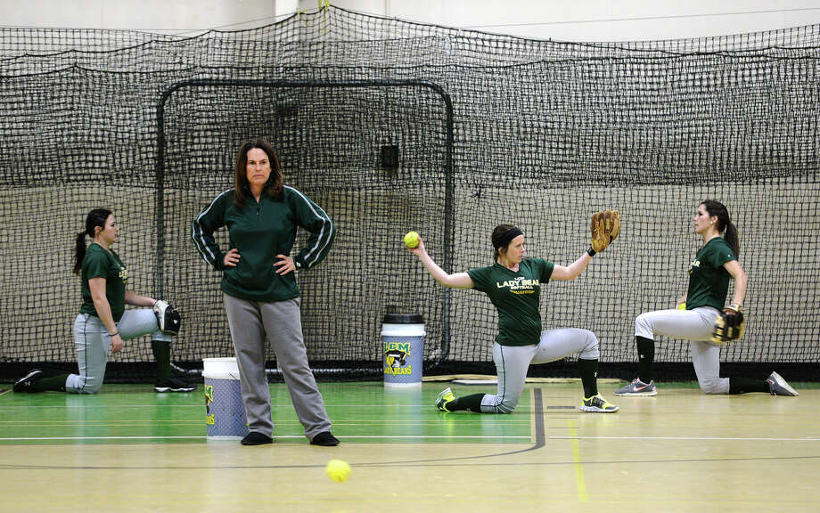 Coach Dena Adkins watches as players practice and stretch out Friday afternoon. Hope Russell, Haley Mills, Morgan Babineaux, and Taylor Fraccastoro, all seniors, pose for a picture in front of the sign for the Little Cypress-Mauriceville High School softball team's 2006 state title Friday afternoon. Photo taken Friday, 2/7/14 Jake Daniels/@JakeD_in_SETX Photo: Jake Daniels / ©2013 The Beaumont Enterprise/Jake Daniels