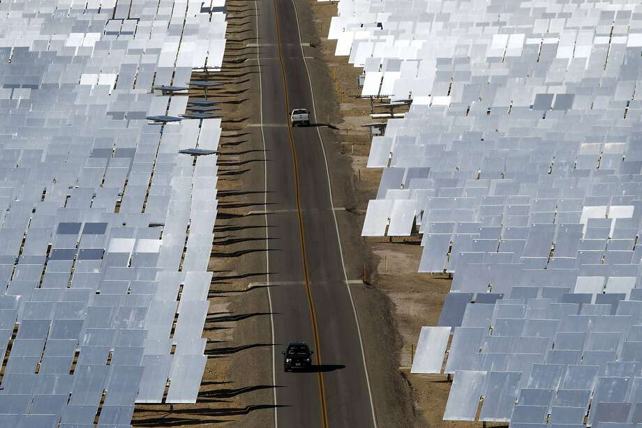 Vehicles drive through field of heliostats (mirrors that track the sun and reflect the sunlight onto a central receiving point) at the Ivanpah Solar Electric Generating System in the Mojave Desert near the California-Nevada border February 13, 2014. The project, a partnership of NRG, BrightSource, Google and Bechtel, is the world's largest solar thermal facility and uses 347,000 sun-facing mirrors to produce 392 Megawatts of electricity, enough energy to power more than 140,000 homes. REUTERS/Steve Marcus (UNITED STATES - Tags: ENERGY BUSINESS SCIENCE TECHNOLOGY) Photo: Steve Marcus, Reuters