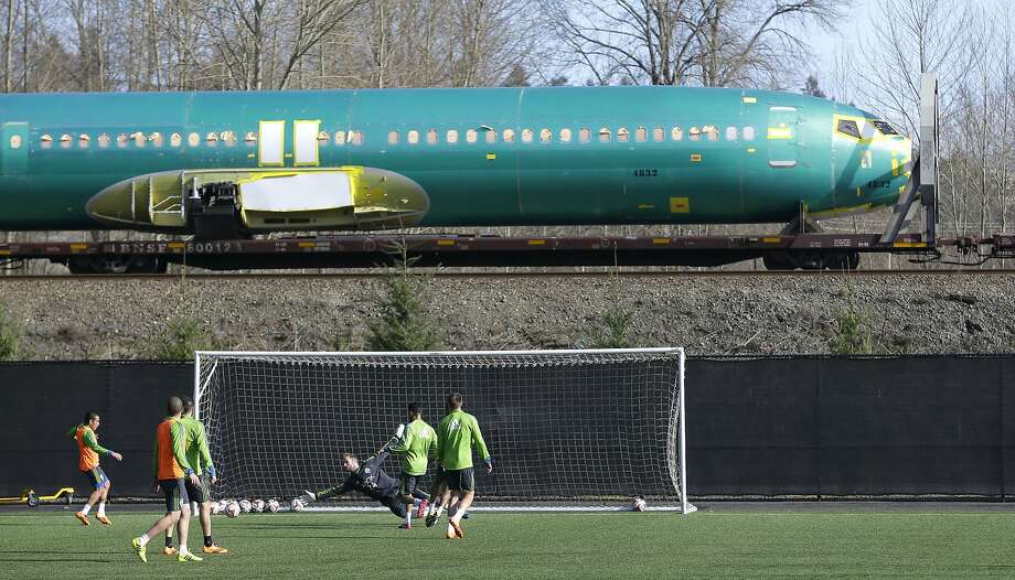 A Boeing 737 fuselage passes by on a railroad car as Seattle Sounders MLS soccer players, including goalkeeper Stephan Frei, take part in a training session, Thursday, Feb. 13, 2014, in Tukwila, Wash. The Sounders open the 2014 regular season on March 8, with a home match against Sporting Kansas City. (AP Photo/Ted S. Warren) Photo: Ted S. Warren, Associated Press