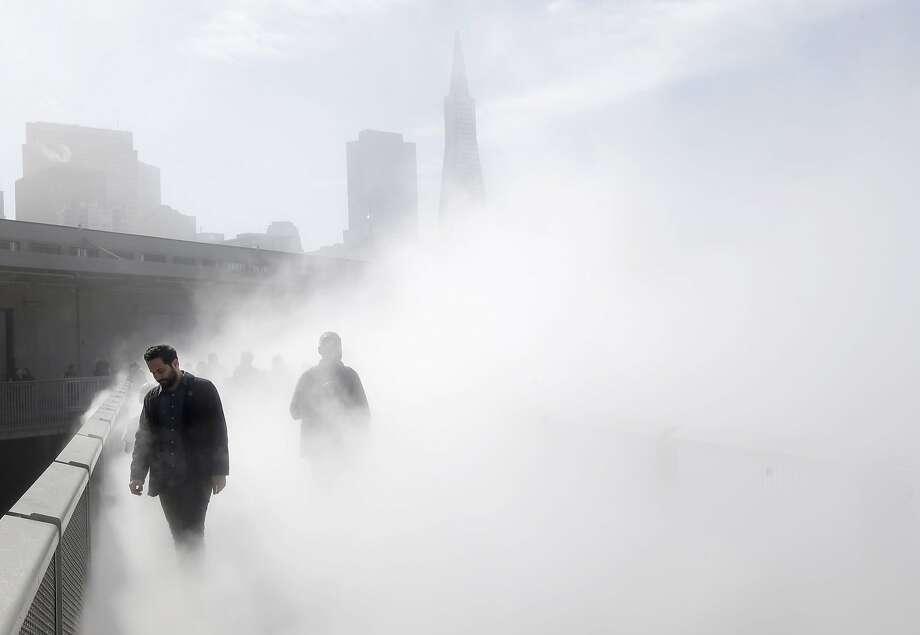 Visitors walk through artist Fujiko Nakaya's Fog Bridge, an artificial fog exhibit, on Thursday, Feb. 13, 2014, at the Exploratorium in San Francisco. (AP Photo/Marcio Jose Sanchez) Photo: Marcio Jose Sanchez, Associated Press