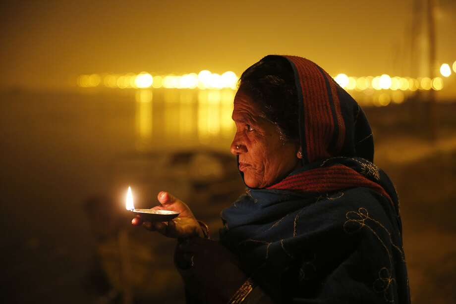 "A Hindu devotee holds an oil lamp to perform evening rituals at ""Sangam,"" the confluence of the Ganges and Yamuna, and mythical Saraswati river, during the annual traditional fair ' Magh Mela' in Allahabad, India, Thursday, Feb. 13, 2014. Hundreds of thousands of devout Hindus are expected to take holy dips at the confluence during the astronomically auspicious period of over 45 days celebrated as Magh Mela. (AP Photo/Rajesh Kumar Singh) Photo: Rajesh Kumar Singh, Associated Press"