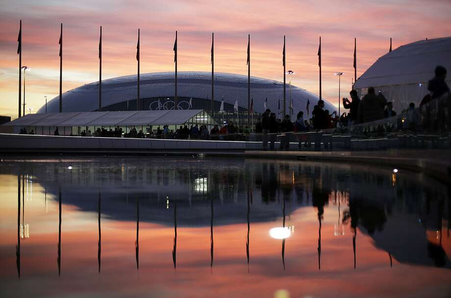 The sun sets as the Bolshoy Ice Dome is reflected in a pool of water underneath the Olympic cauldron at the 2014 Winter Olympics, Thursday, Feb. 13, 2014, in Sochi, Russia. (AP Photo/David Goldman) Photo: David Goldman, Associated Press
