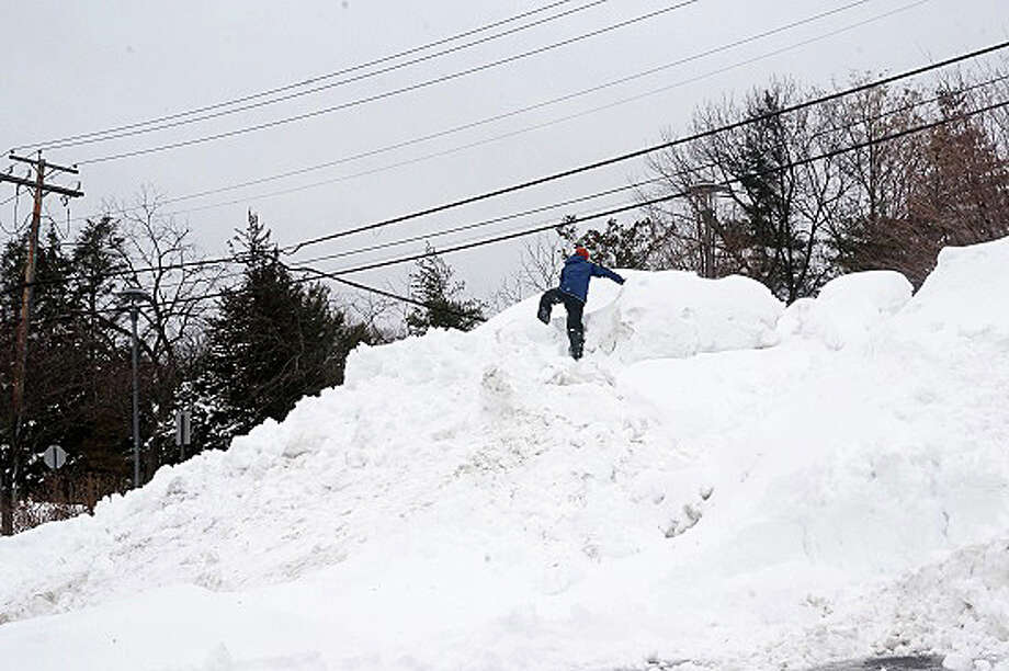 "One kid scaled ""Mount Fairfield"" on Thursday afternoon -- otherwise known as the snow pile amassed by plows clearing the parking lot at Roger Ludlowe Middle School. Photo: Genevieve Reilly / Fairfield Citizen"
