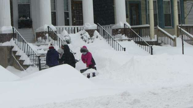Children shovel snow on Delaware Avenue in Albany on Friday, Feb. 14, 2014. A nor'easter that socked the East Coast with snow and ice dumped snow on the Capital Region. (Bob Gardinier / Times Union)