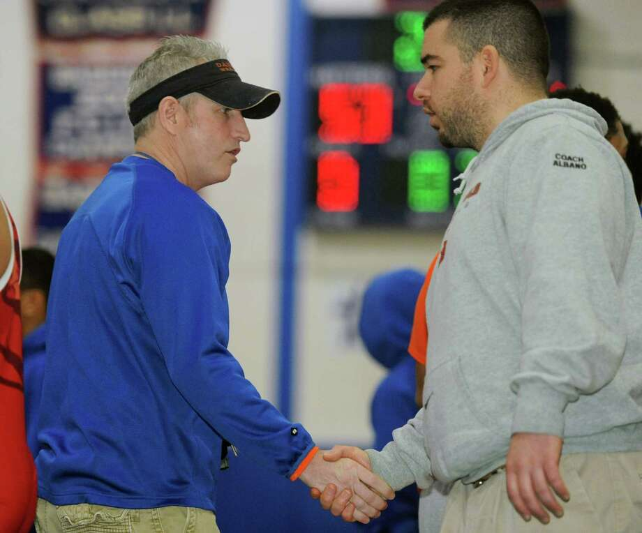 Danbury wrestling coach Rick Shook, left, shakes hands after the wrestling match between between Danbury and Greenwich as part of the meet between Danbury, New Milford, Greenwich, Darien, Xavier and Harding at Danbury High School in Danbury, Conn. on Saturday, Feb. 8, 2014. Photo: Tyler Sizemore / The News-Times