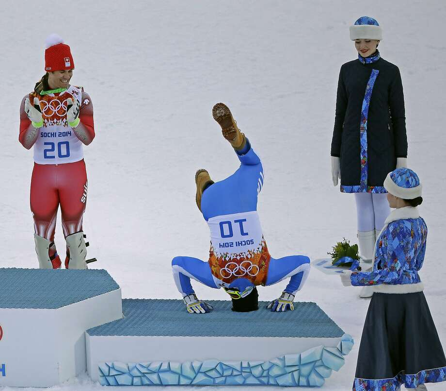Bronze medalist Italy's Christof Innerhofer does a backflip onto the podium while gold medalist Switzerland's Sandro Viletta watches during the flower ceremony for the men's supercombined at the 2014 Winter Olympics, Friday, Feb. 14, 2014, in Krasnaya Polyana, Russia. Photo: Charlie Riedel, Associated Press