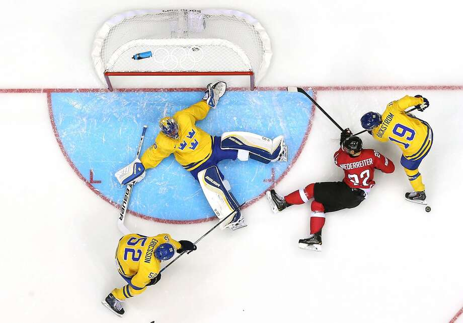 Henrik Lundqvist #30 of Sweden makes a save against Nino Niederreiter #22 of Switzerland in the first period during the Men's Ice Hockey Preliminary Round Group C game on day seven of the Sochi 2014 Winter Olympics at Bolshoy Ice Dome on February 14, 2014 in Sochi, Russia. Photo: Bruce Bennett, Getty Images