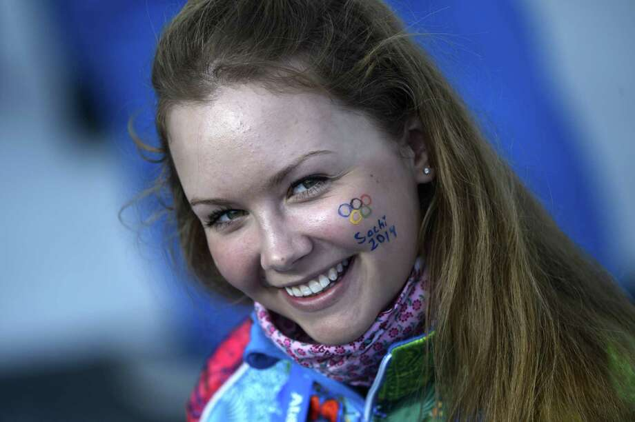 A volunteer has Sochi2014 painted on her cheek before the Men's Cross-Country Skiing 15km Classic at the Laura Cross-Country Ski and Biathlon Center during the Sochi Winter Olympics on February 14, 2014 in Rosa Khutor near Sochi. Photo: PIERRE-PHILIPPE MARCOU, AFP/Getty Images / 2014 AFP