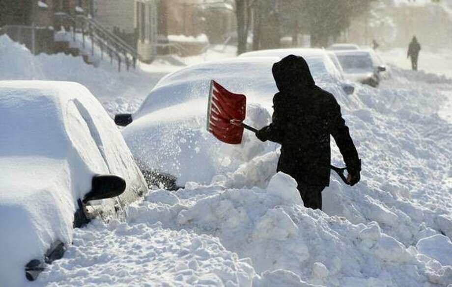Ricardo Lopez digs out on Washington Avenue in Albany to get to work on Friday, Feb. 14, 2014. (Skip Dickstein / Times Union)