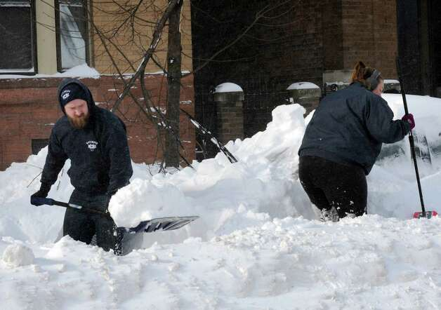 Jordan Rozell, left, and Paige Wood dig out their car on Madison Avenue Friday Feb. 14, 2014 in Albany, N.Y. (Michael P. Farrell/Times Union) Photo: Michael P. Farrell / 00025756A