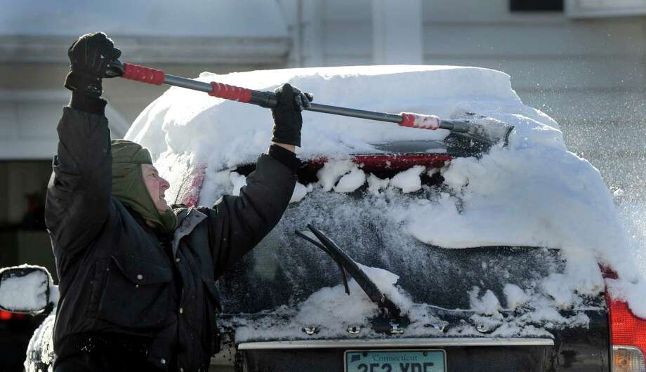Frank DeMunda, 69, clears the snow from his car on Regen Road in Danbury, Conn., Friday morning, Feb. 14, 2014, after an overnight snowfall. Photo: Carol Kaliff / The News-Times