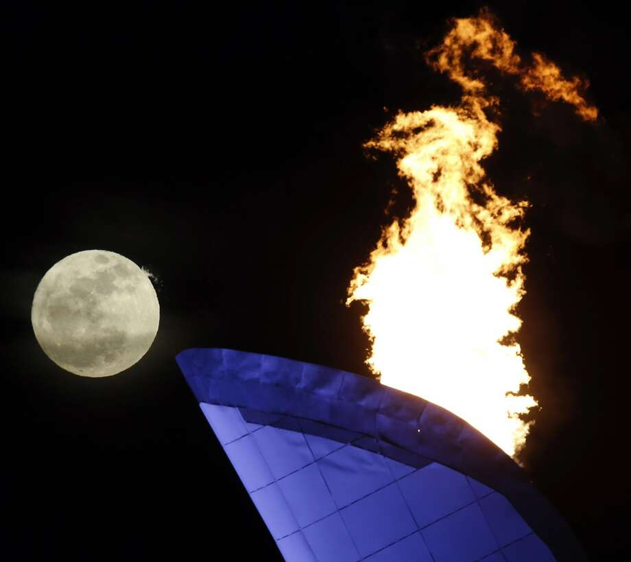 The moon rises near the Olympic cauldron as the Olympic Flame burns in the background at the 2014 Winter Olympics, Friday, Feb. 14, 2014, in Sochi, Russia. Photo: Julio Cortez, Associated Press
