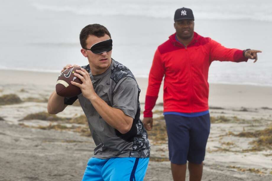Johnny Manziel does a passing drill blindfolded with quarterback trainer George Whitfield while working out on Mission Beach in preparation for the NFL draft. Photo: Brett Coomer, Houston Chronicle