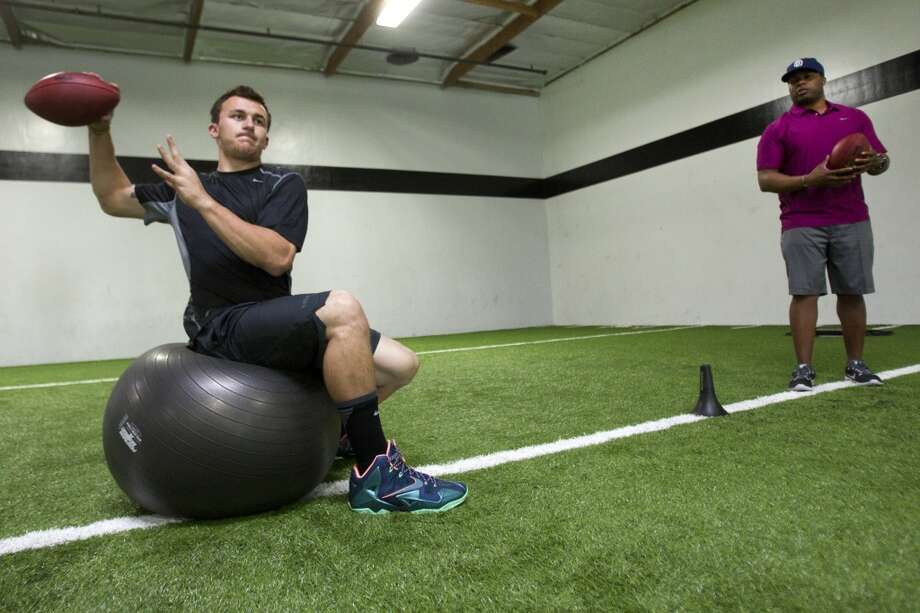 Johnny Manziel throws a pass as quarterback trainer George Whitfield looks on while working out in preparation for the NFL draft. Photo: Brett Coomer, Houston Chronicle