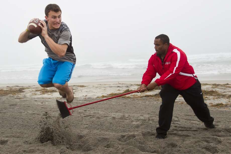Johnny Manziel leaps over a broom while working out with Hank Speights on Mission Beach in preparation for the NFL draft. Photo: Brett Coomer, Houston Chronicle