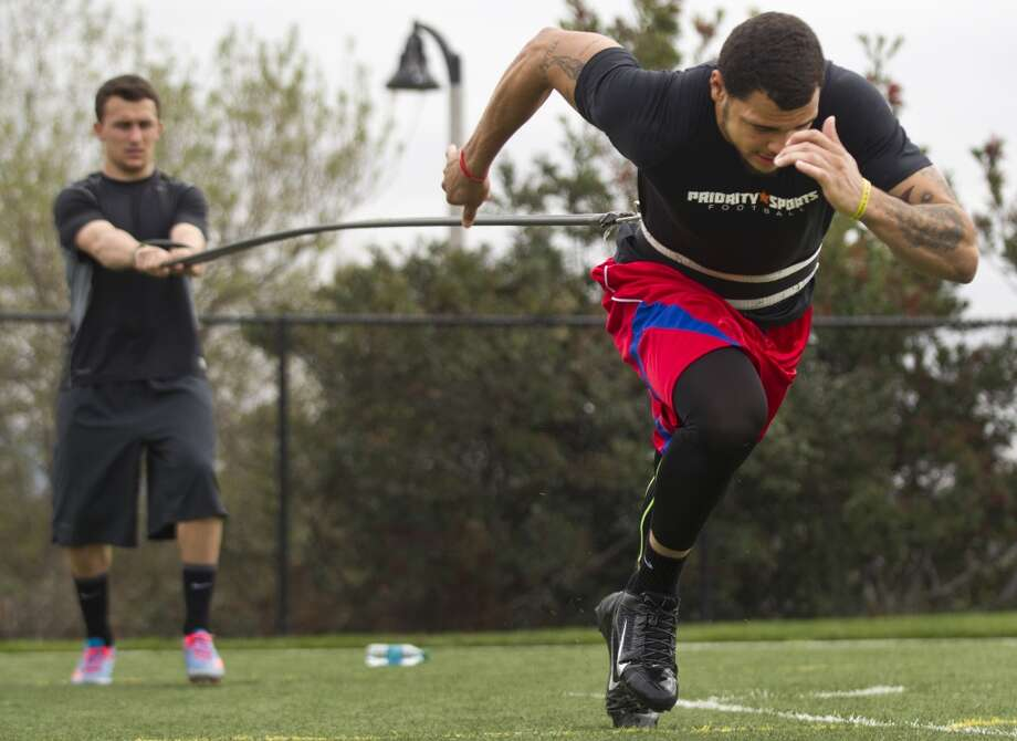 Former Texas A&M wide receiver Mike Evans runs a sprint, being held back with a giant rubber band by Johnny Manziel while working out in preparation for the NFL draft. Photo: Brett Coomer, Houston Chronicle