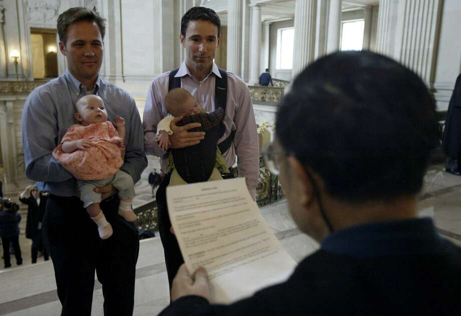 Feb. 13, 2004: Holding the twin daughters Sophia and Elizabeth, Eric Etherington (left) exchanges marriage vows with Doug Okun in front of marriage commissioner Richard Ow. Same sex couples waited up to two hours to get legally married at City Hall in San Francisco. Photo: Paul Chinn, The Chronicle