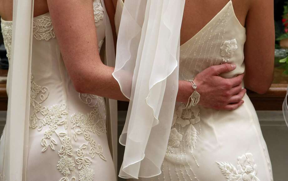 June 17, 2008: Amber Weiss, left, and Sharon Papo,  wait in line in their wedding dresses, to complete paperwork for their marriage certificate at City Hall in San Francisco. With a quiet pride and a sense of history, hundreds of gay and lesbian couples across California wed on Tuesday, giving a human face to a landmark court decision and a powerful opening salvo in what is expected to be a bruising fall campaign here over the issue of same-sex marriage. Photo: Michael Macor, The Chronicle