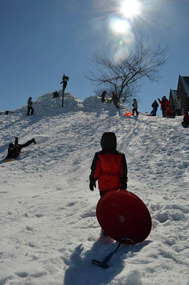 Curtis Sullivan, 8, foreground, contemplates the climb back up the hill after zipping downhill on Friday's fresh snow at Greens Farms Elementary School. Photo: Jarret Liotta / Westport News contributed