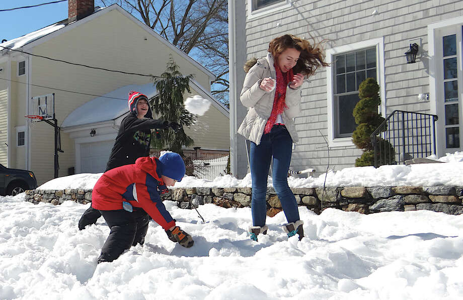 Snowball battle erupts Friday between siblings Cole, Troy and Julia Spencer, ages 11, 6 and 13, respectively, in front of their Fern Street home. Photo: Mike Lauterborn / Fairfield Citizen contributed