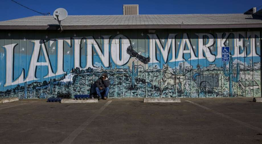 California: A man sits outside the Latino Market in Mendota, California, U.S., on Tuesday, Feb. 11, 2014. Photo: Ken James, Bloomberg