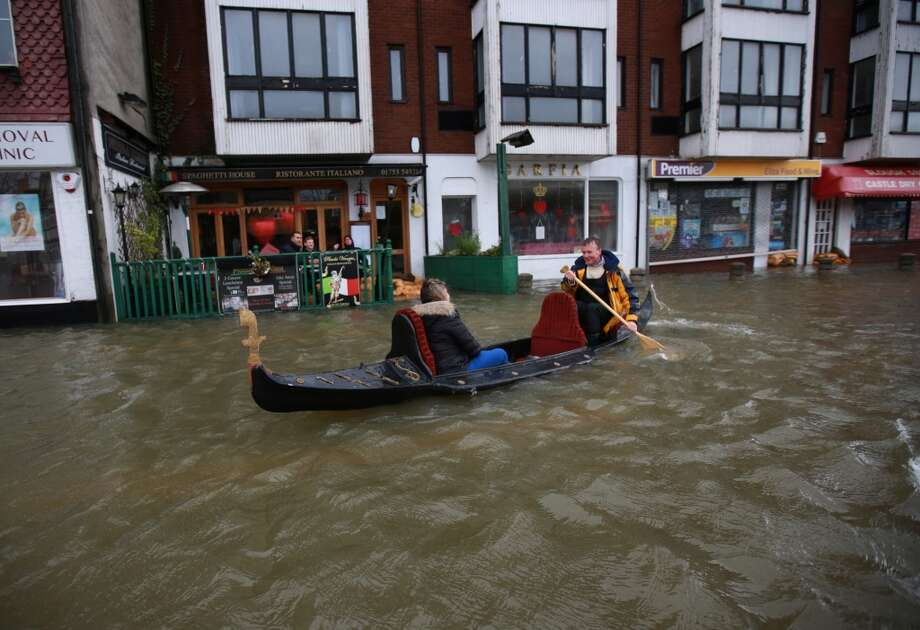 United Kingdom: A couple promote the Piccola Venezia Italian restaurant by rowing their gondola through flood waters on February 12, 2014 in Datchet, England. Photo: Peter Macdiarmid, Getty Images