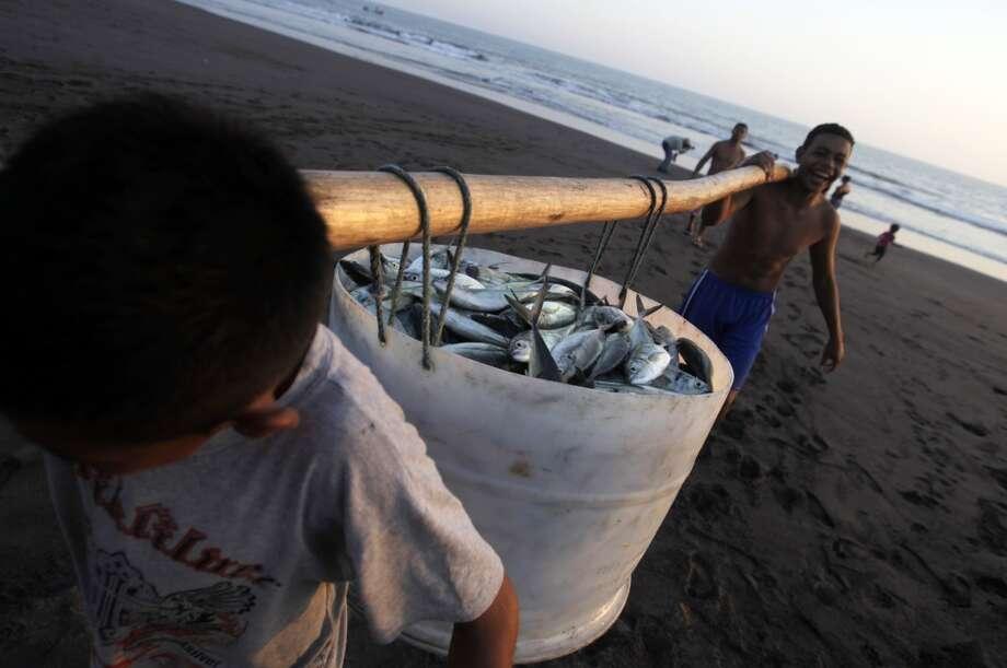 El Salvador: Boys carry a bucket with fish. Photo: Jorge Cabrera, Reuters