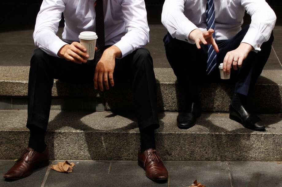 Australia: Office workers sit with cups of coffee at Martin Place in the central business district of Sydney, Australia. Photo: Brendon Thorne, Bloomberg