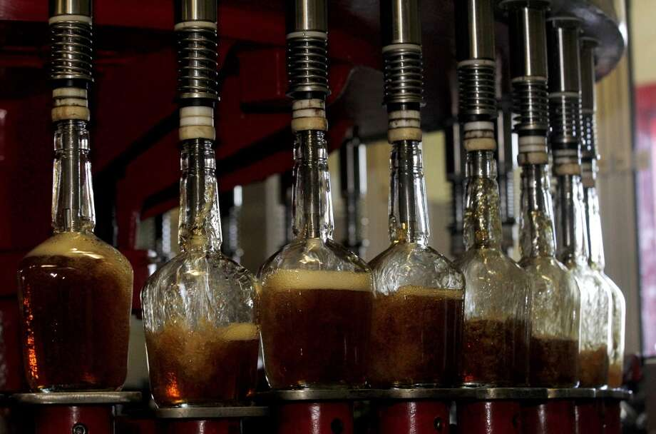 Kentucky: Maker's Mark bottles are filled with with bourbon on the production line at the Maker's Mark Distillery plant in Loretto, Kentucky. Suntory Holdings Ltd said on January 13 that it would buy U.S. spirits company Beam Inc for $13.6 billion cash in a deal that would make the Japanese company the world's third-largest spirits maker. Photo: John Summers II, Reuters