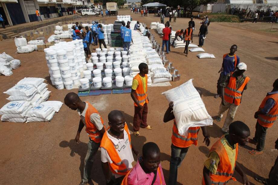 Central African Republic: Aid workers unload food to be distributed at a camp for people displaced by the recent unrest, at the Mpoko international airport of Bangui February 12, 2014. The United Nations estimates that 1.3 million people - more than a quarter of the population - are in need of urgent food aid after months of communal violence that French and African peacekeepers have been unable to stop. Photo: Luc Gnago, Reuters