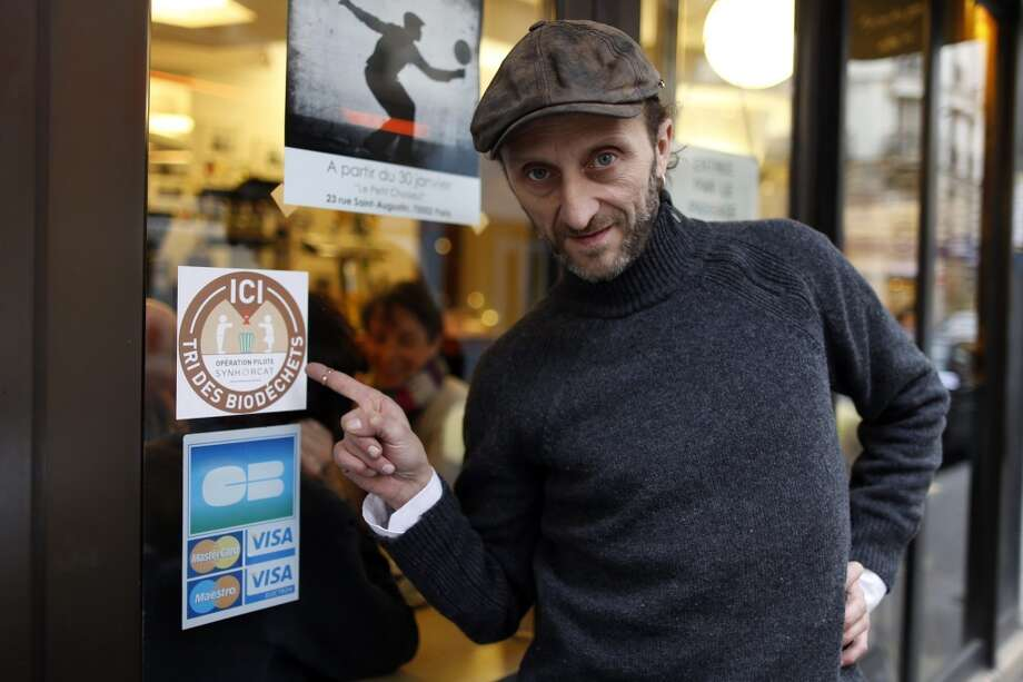 France: Stephan Martinez, owner of Le Petit Choiseuil bistrot, points at a sticker for a pilot project to collect food waste in Paris February 12, 2014. A group of Paris restaurants is turning food scraps into biogas and compost ahead of a new law that will force thousands of French food outlets to recycle their organic waste. Some 80 restaurants, caterers and hotels, signed up for a pilot project to collect their food waste, which is used to generate biogas and produce electricity and heat, as well as compost for farms around Paris. Martinez, who took the initiative for the project, said the collection anticipates the law but that participating restaurants are happy that someone collects their waste and puts it to good use. Photo: Charles Platiau, Reuters