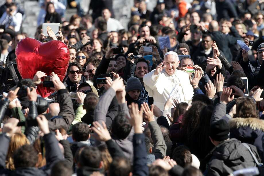 Pope Francis waves to engaged couples gathered in St. Peter's Square for an audience on the subject of marriage. About 25,000 people from 30 countries attended the St. Valentine's Day event. Photo: Franco Origlia, Getty Images