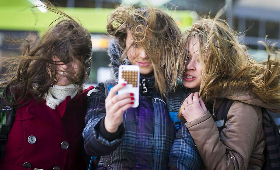 Gee, your hair looks horrific: Eastern Washington University students Annette Bovdyr (left), Valeriya Mokrushina and Julia Mokrushina document their windswept coifs with a selfie while waiting for a bus in downtown Spokane. Photo: Colin Mulvany, Associated Press