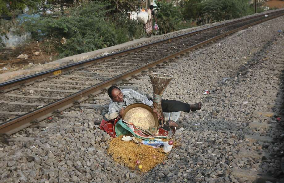 Derailment on the main line: An Indian food vendor trips and spills his bowl of chudwa while crossing the railroad tracks in Hyderabad, India. Chudwa is a rice flakes mixture served with a blend of nuts and dried fruits. Photo: Mahesh Kumar A., Associated Press