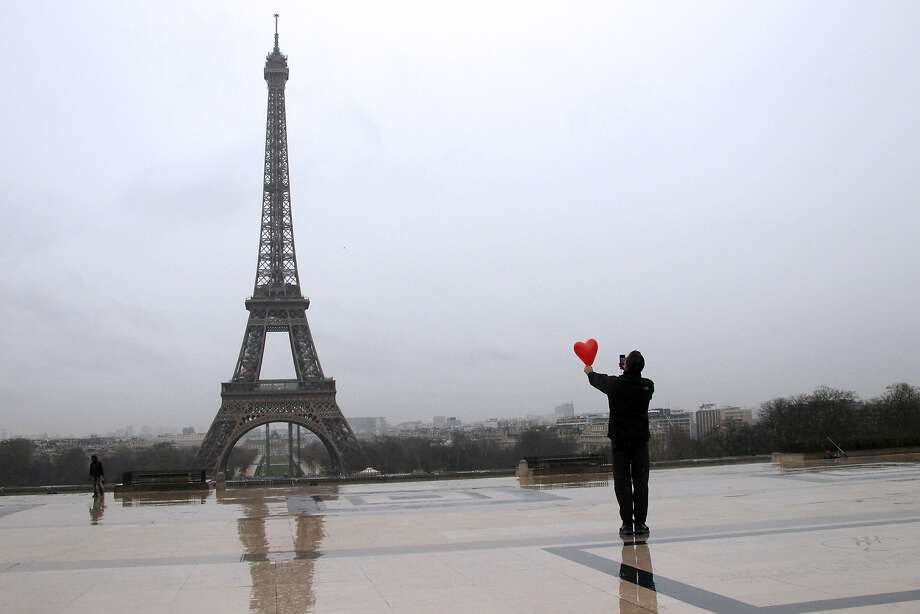 Le coeur Eiffel:A man holding a heart in his hand takes a picture of Paris' most famous landmark on Valentine's Day. Photo: Ludovic Marin, AFP/Getty Images
