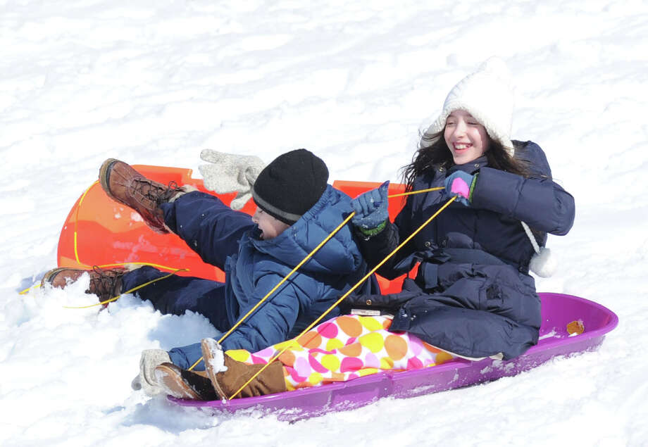 At right, Eugenia Rem, 9, of Greenwich, crashes into her twin brother, Carmine, while sledding on a hill in Bruce Park during the aftermath of the snowstorm that hit Greenwich, Friday, Feb. 14, 2014. The National Weather Service is calling for another 2-4 inches of snow on Saturday. Photo: Bob Luckey / Greenwich Time