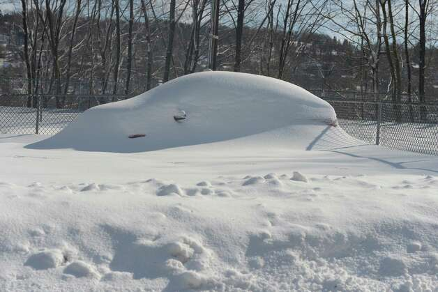 A snow covered car in Derby, Conn. Friday, Feb. 14, 2014. Photo: Autumn Driscoll / Connecticut Post