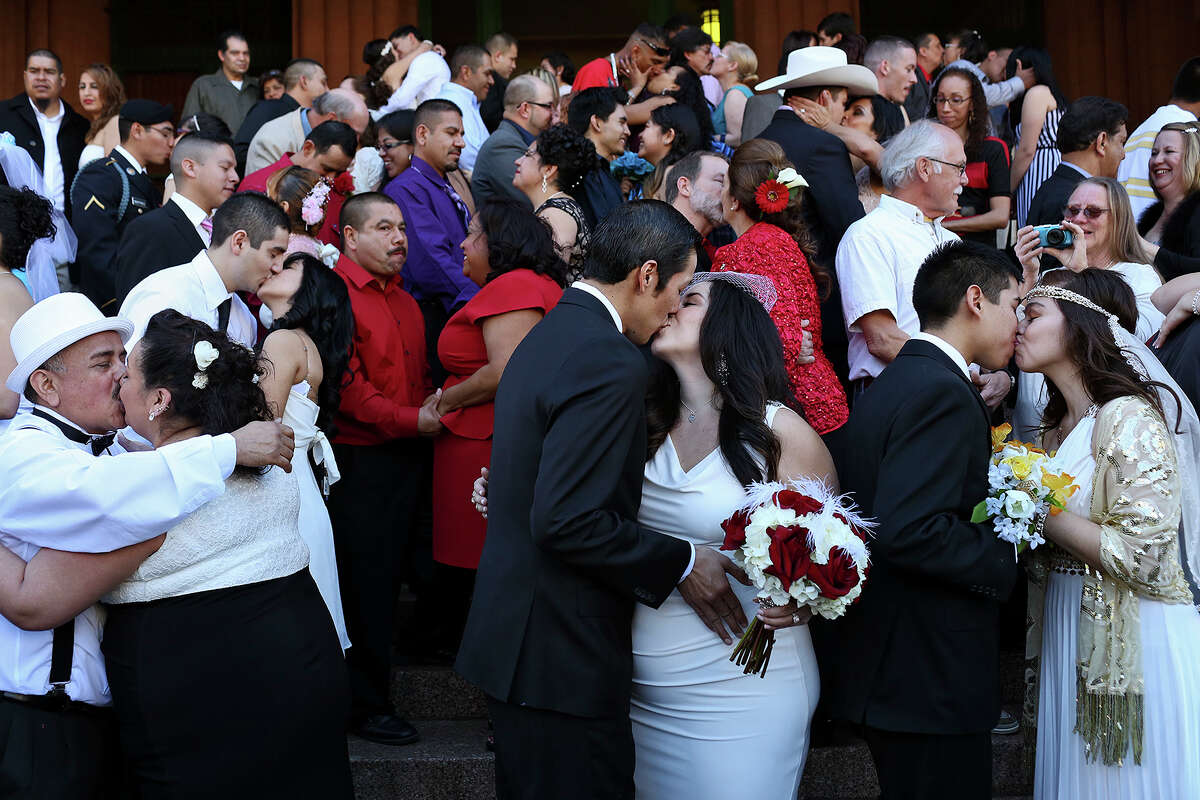 Couples including Oscar Palacios with Matilde Martinez, from left, Anthony Sanchez with Stephanie Hernandez, and Analicia Vazquez with John Vazquez, kiss after saying their vows during a mass wedding on the steps of the Bexar County Courthouse in San Antonio on Friday, Feb. 14, 2014.
