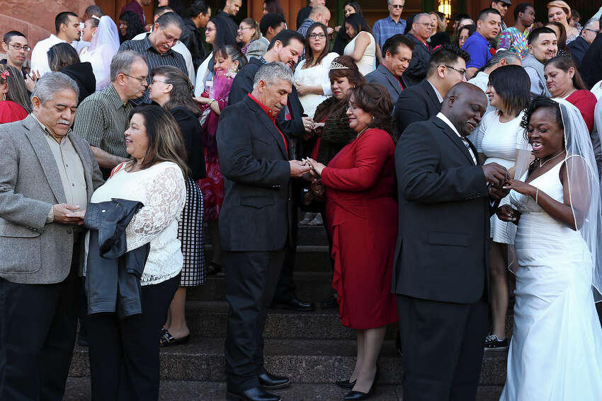 Couples including David and Dianna Flores, who have been married for 33 years and renewed their vows, Edgar and Ernestina Gonzalez, and Lonnie Hines with Erma Prince, get married during a mass wedding on the steps of the Bexar County Courthouse in San Antonio on Friday, Feb. 14, 2014.