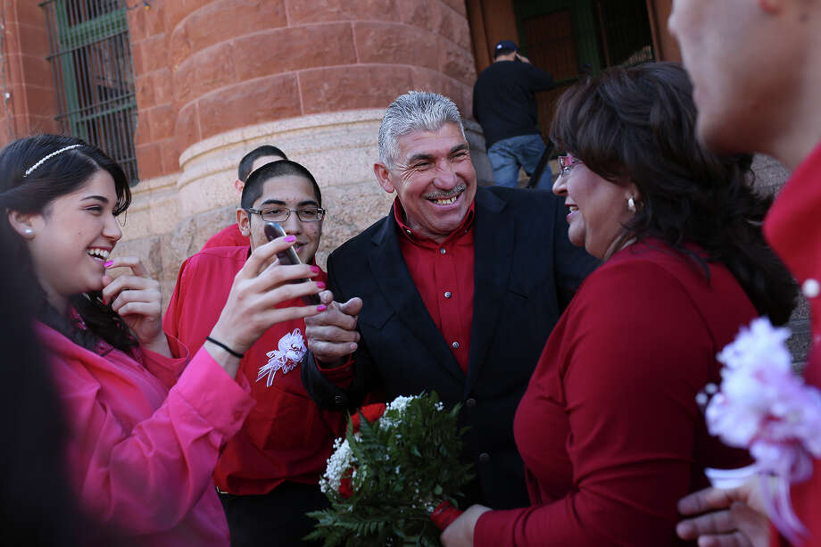Ernestina and Edgar Gonzalez, right, laugh with Edgar's children, Taylor Gonzalez, far left, and Matthew Gonzalez, after they got married in a mass wedding on the steps of the Bexar County Courthouse in San Antonio on Friday, Feb. 14, 2014. Photo: LISA KRANTZ, SAN ANTONIO EXPRESS-NEWS / SAN ANTONIO EXPRESS-NEWS