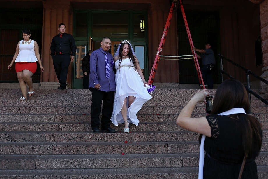 Brandi Luna and Heriberto Herrera pose for her sister, Phyllis Settles to take a picture as fellow newlyweds Sara Flores and Gabriel Fraga, left, walk by after they were married in a mass wedding on the steps of the Bexar County Courthouse in San Antonio on Friday, Feb. 14, 2014. Photo: LISA KRANTZ, SAN ANTONIO EXPRESS-NEWS / SAN ANTONIO EXPRESS-NEWS