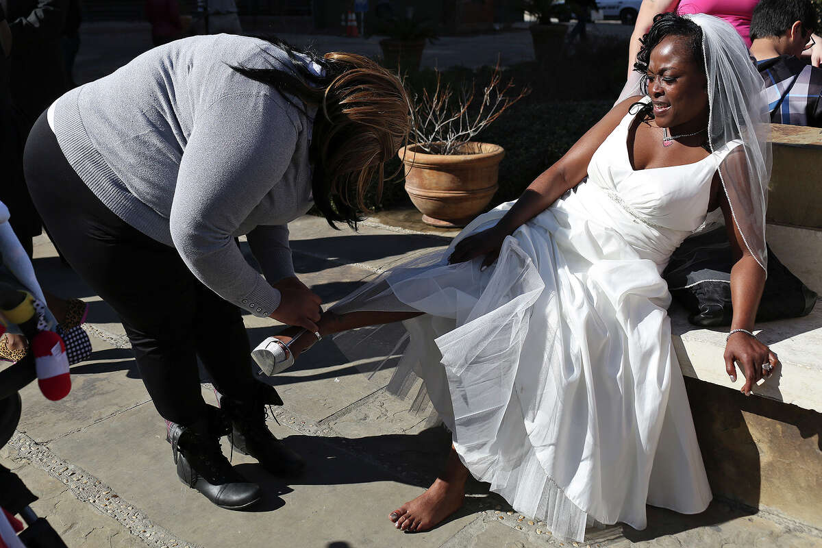 Erma Prince gets help taking her shoes off from her daughter, Deni Hines, after Erma married Lonnie Hines during a mass wedding on the steps of the Bexar County Courthouse in San Antonio on Friday, Feb. 14, 2014. The couple has been together for 14 years.