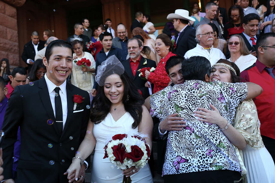 Anthony Sanchez, from left, with Stephanie Hernandez (now Sanchez) and Analicia Vazquez with John Vazquez, greet their families and friends after getting married during a mass wedding on the steps of the Bexar County Courthouse in San Antonio on Friday, Feb. 14, 2014. Photo: LISA KRANTZ, SAN ANTONIO EXPRESS-NEWS / SAN ANTONIO EXPRESS-NEWS