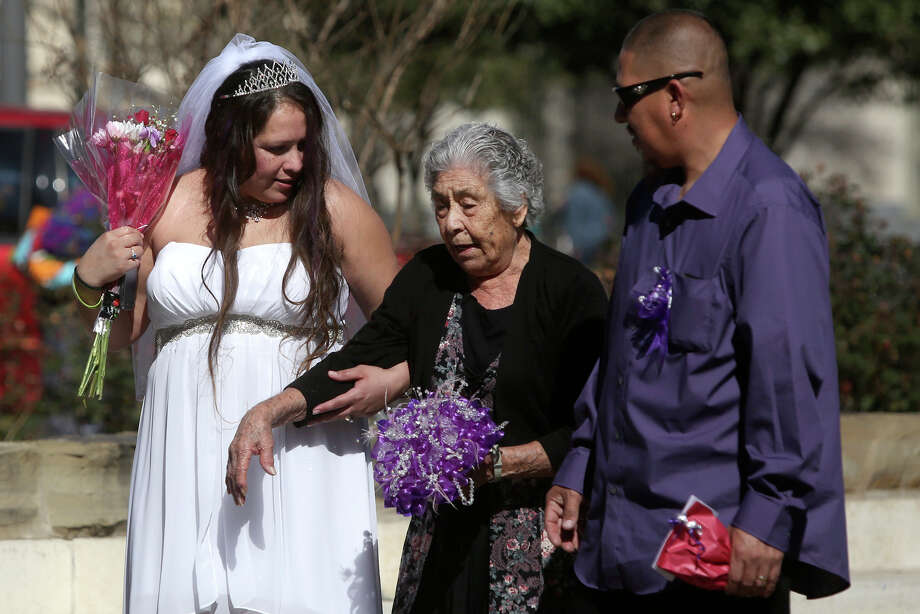 Brandi Luna and her husband, Heriberto Herrera, walk with her grandmother, Emilia Luna, 81, after they were married in a mass wedding on the steps of the Bexar County Courthouse in San Antonio on Friday, Feb. 14, 2014. Photo: LISA KRANTZ, SAN ANTONIO EXPRESS-NEWS / SAN ANTONIO EXPRESS-NEWS