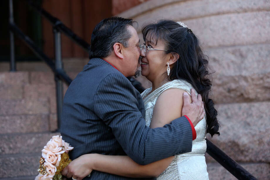 Jaime Muniz and Martha Flores kiss and joke around with each other after becoming husband and wife during a mass wedding on the steps of the Bexar County Courthouse in San Antonio on Friday, Feb. 14, 2014. The couple surprised her mother with the ceremony, telling her she was going to a Valentine's Day party and is surprising their family and friends later with the news. Photo: LISA KRANTZ, SAN ANTONIO EXPRESS-NEWS / SAN ANTONIO EXPRESS-NEWS