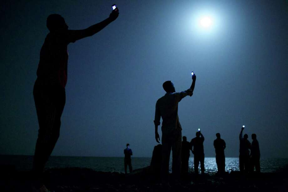 John Stanmeyer won the World Press Photo of the Year 2013 for this photo of African migrants on the shore of Djibouti city at night, raising their cellphones in an attempt to capture an inexpensive signal from neighboring Somalia. Photo: John Stanmeyer, HONS / World Press Photo