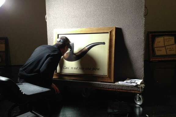 """Joe Fronek, head paintings conservator from the Los Angeles County Museum of Art, examined one of the most iconic paintings in the exhibit """"Magritte: Mystery of the Ordinary"""" after it arrived at the Menil Collection."""