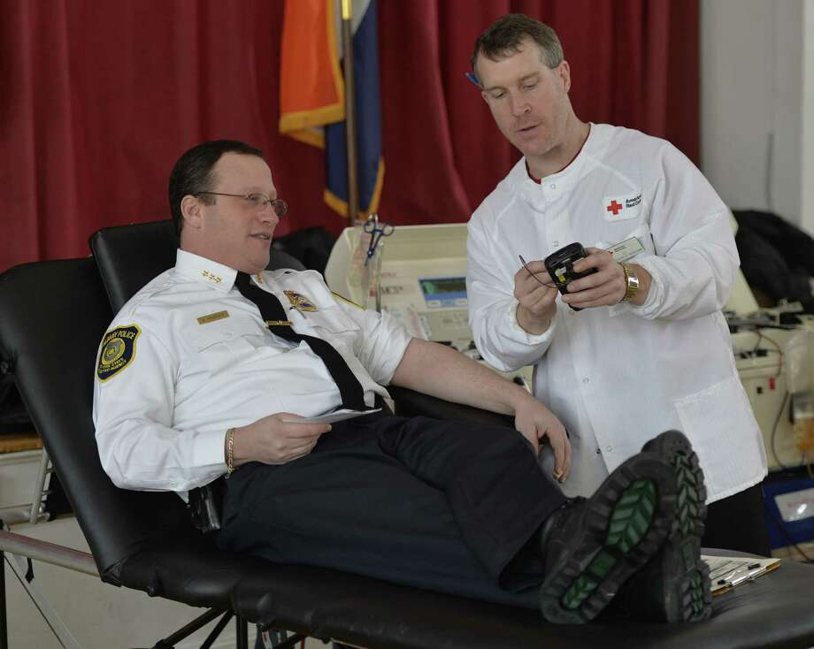 Albany Police Chief Steve Krokoff, left, is prepped by Red Cross supervisor Ed Small before giving blood during the 10th annual Lt. John Finn Blood Drive Friday morning, Feb. 14, 2014, in Albany, N.Y.  Lt. John Finn was shot  in the line of duty and succumbed to his injuries on Feb. 14, 2004.  (Skip Dickstein/ Times Union) Photo: Skip Dickstein / 00025646A